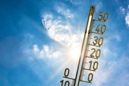 Hitzewelle, Thermometer mit strahlender Sonne und blauem Himmel